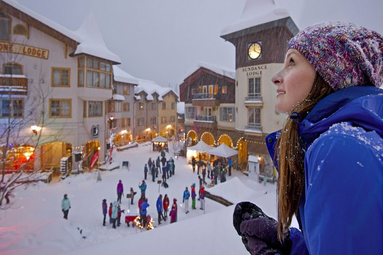 A young woman watches the snow falling and village activity from above at Sun Peaks, near Kamloops, British Columbia, Canada