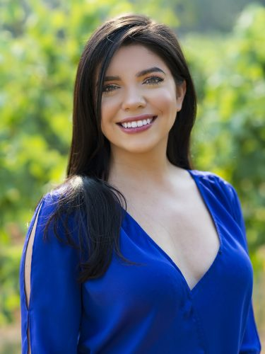 A beautiful young lady poses for a portrait in a vineyard in Kelowna, British Columbia, Canada