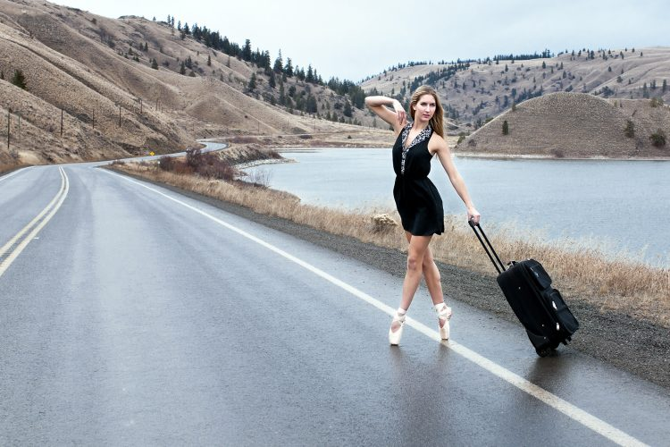 A beautiful young woman poses on the highway during a ballet commercial shoot, south of Kamloops, Thompson Okanagan region, British Columbia, Canada