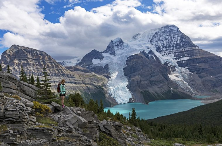 A young woman takes in the view of Mt. Robson and Berg Lake during a tourism shoot, Mt. Robson Provincial Park, BC, Canada