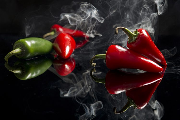 Red peppers in the studio with smoke, during a commercial food shoot, Vancouver, British Columbia, Canada
