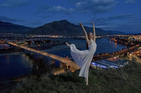 A young, beautiful ballet dancer poses over the city of Kamloops at dusk, Thompson Okanagan region of British Columbia, Canada