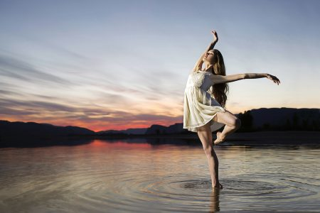 A young ballet dancer strikes a pose during a beautiful sunset on the Thompson river, west of Kamloops, Thompson Okanagan region, British Columbia, Canada