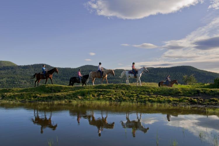 A group of horseback riders make their way along the shores of a small lake, near the community of Pinantan lake, near Kamloops in the Thompson Okanagan region of British Columbia, Canada