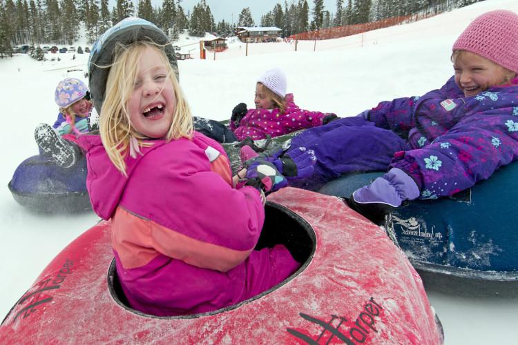 Kids tubing down a ski run at Harper mnt, Kamloops, BC Thompson Okanagan region, Canada