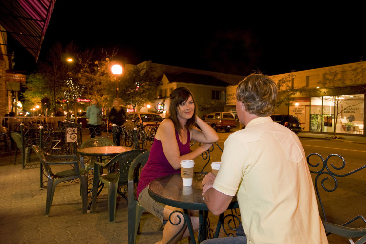 A young couple stop for a drink at a coffee house, while enjoying an early evening shopping trip in downtown Kamloops, in the Thompson Okanagan region of British Columbia, Canada.