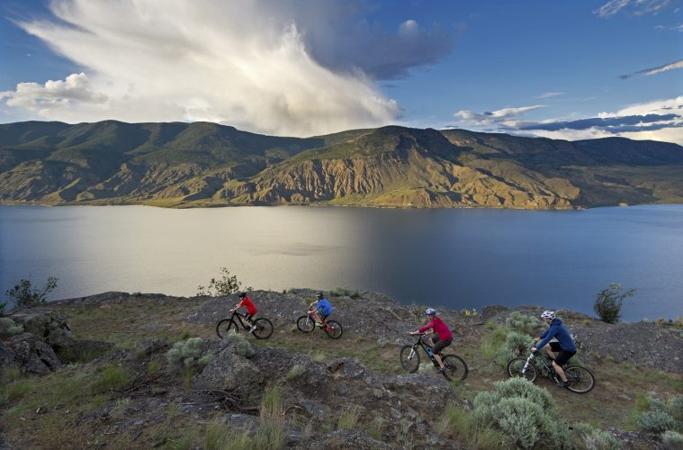 A family rides a ridge on the south side of Kamloops lake during a tourism photo shoot, near Kamloops, Thompson Okanagan region, British Columbia, Canada