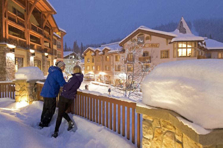 A young man and woman look out over Sun Peaks Resort from the balcony of the Sun Peaks Grand and Conference centre on a snowy, winter night, Thompson Okanagan region, British Columbia, Canada