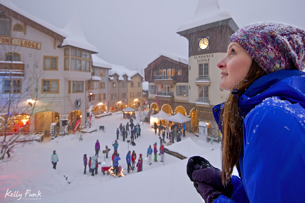 A young woman enjoys the views in the village of Sun Peaks during a snowfall and commercial photography shoot, Thompson Okanagan region, British Columbia, Canada