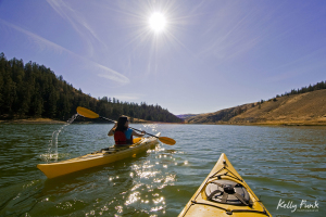 A young women takes the lead while kayaking on a beautiful sunny day at Trapp lake, near Kamloops, British Columbia Canada