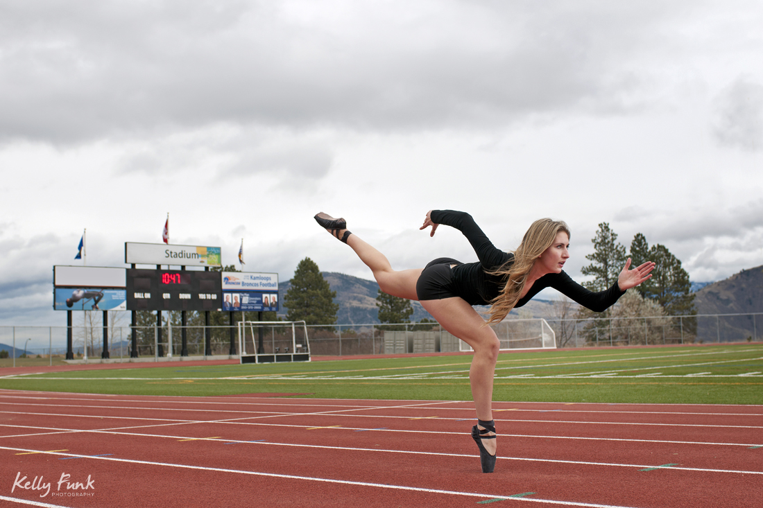 A female ballet dancer uses her athleticism on the track, creating a running pose at Kamloops, Thompson Okanagan region of British Columbia, Canada