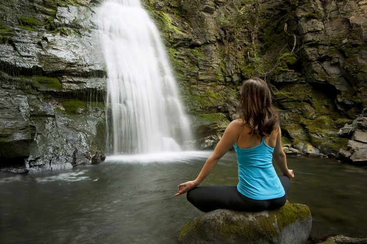 A yoga instructor performs a pose in front of a waterfall near Sun Peaks Resort, north of Kamloops, British Columbia, Canada