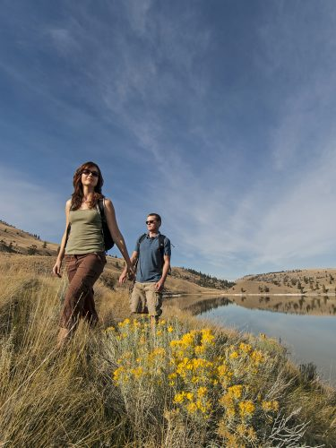 A male and female pair of hikers enjoy the Thompson Okanagan grasslands, south of Kamloops at Trapp lake, British Columbia, Canada