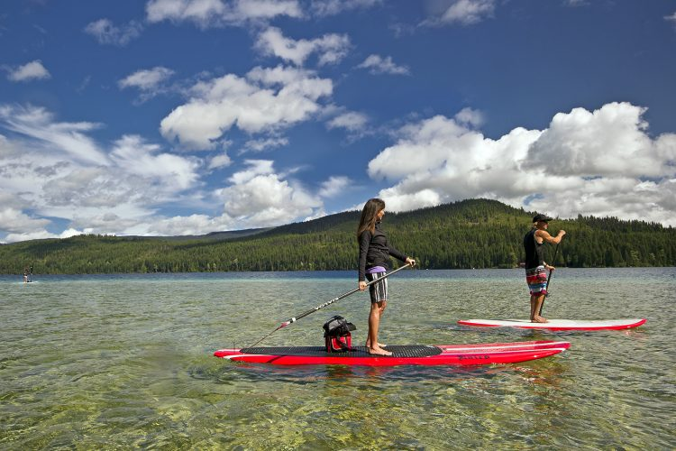 Stand up paddlers enjoy Johnson Lake, south of Barriere, Thompson Okangan region, British Columbia, Canada