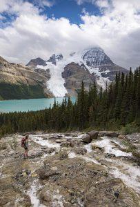A hiker stands near Toboggan falls near Berg Lake, Mt. Robson Provincial park, British Columbia, Canada