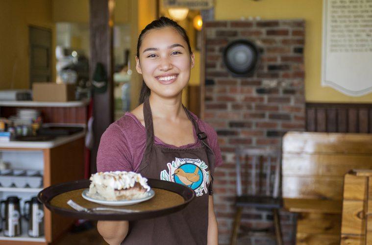 A beautiful young woman serves pie inside a restaurant in Vanderhoof, British Columbia, Canada