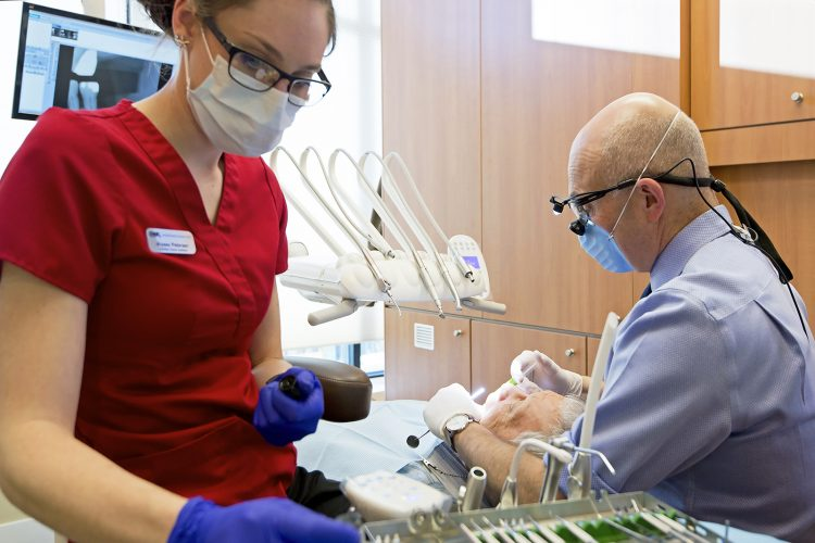 A dentist and assistant care for a patient during an appointment at a clinic in Kamloops, British Columbia, Thompson Okanagan region, Canada