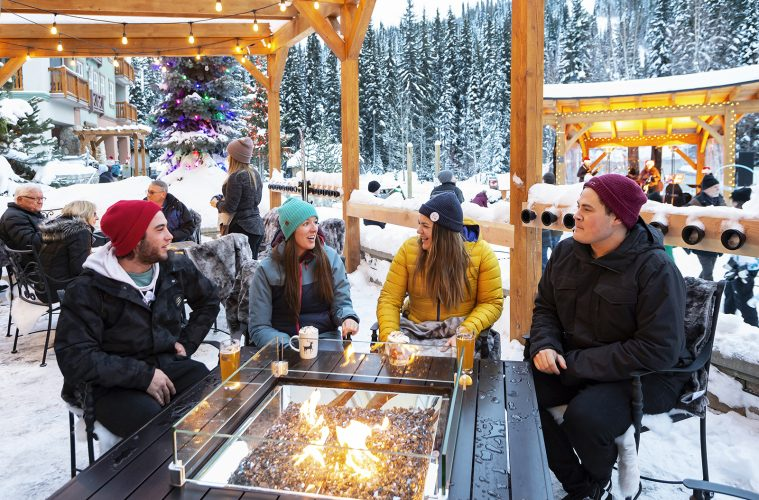 A group of friends enjoy the fire pit patio at Sun Peaks Resort, north east of Kamloops, British Columbia, Thompson Okanagan region, Canada