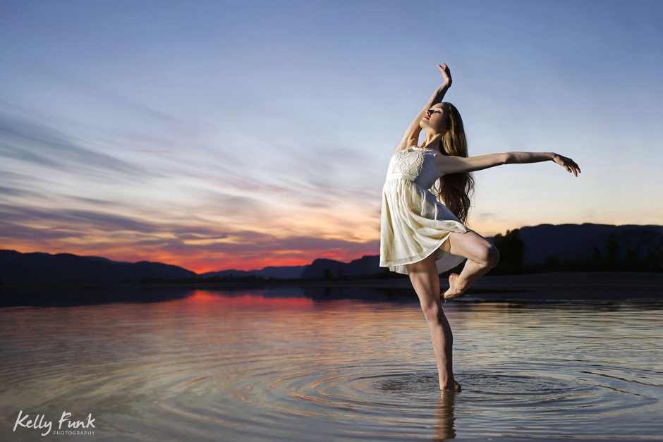 Ballerina dancer strikes a beautiful pose in the Thompson river, at sunset near Kamloops, British Columbia, Canada