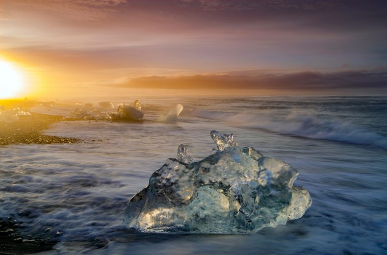 Glacial Ice washes up on the shores of the Atlantic ocean at the southern end of Iceland, Europe at sunrise.
