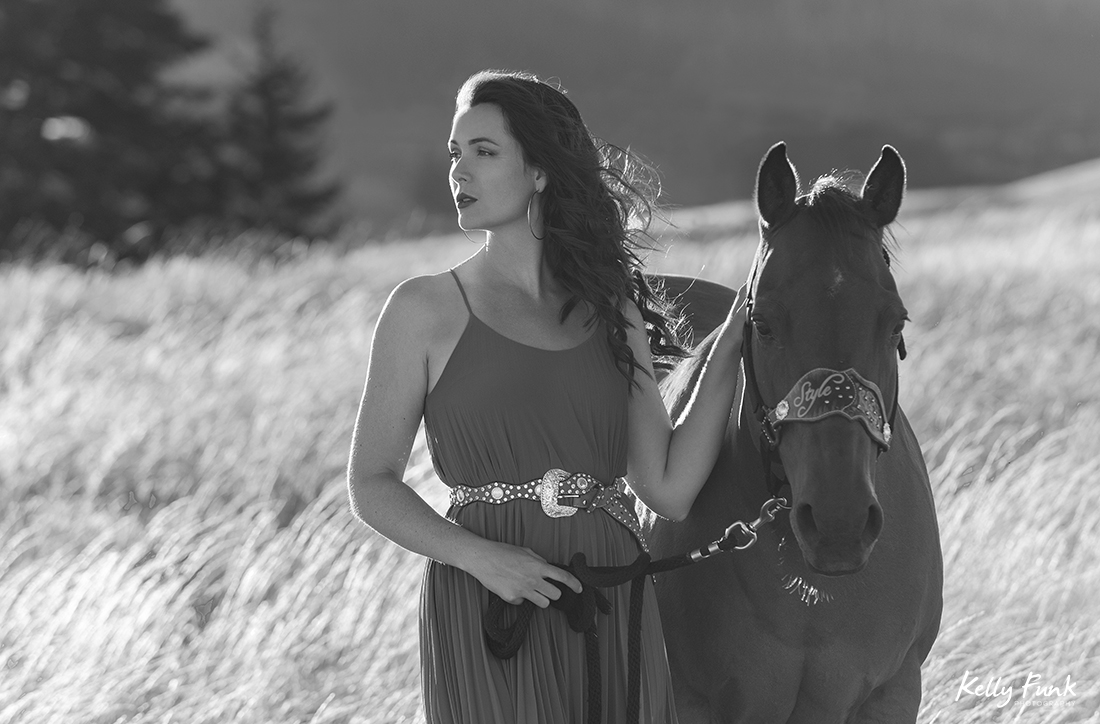 A beautiful woman and her horses walk the fields at sunset for a portrait during sunset on the ranch near Kamloops, British Columbia, Canada