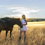 A beautiful woman and her horse pose in a field at sunset for a portrait during sunset on the ranch near Kamloops, British Columbia, Canada