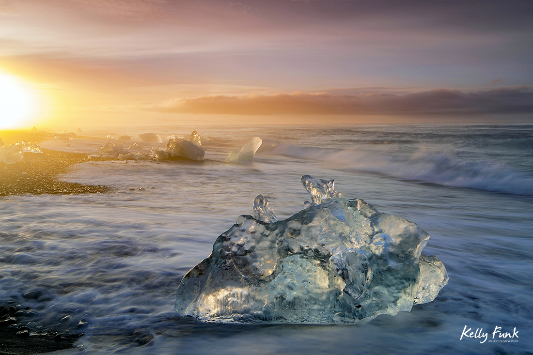 Pieces of Glacier from Jökulsárlón, a glacial lagoon, bordering Vatnajökull National Park in southeastern Iceland lay on the black sands of the Atlantic at sunrise, following high tide