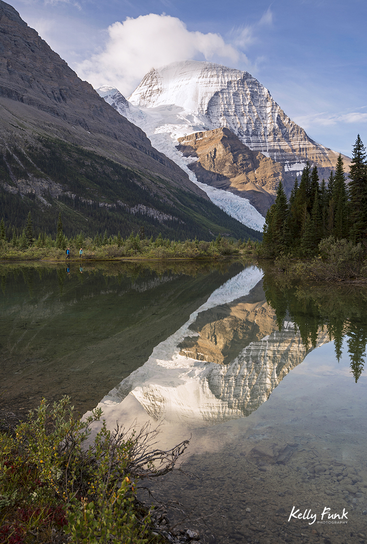 Two hikers explore a small pond at the foot of Mount Robson, Canadian Rockies, British Columbia