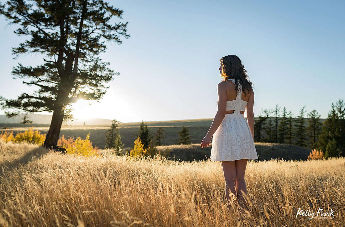 A beautiful young woman enjoys a gorgeous sunset in the grasslands of British Columbia, Canada during a commercial photo shoot