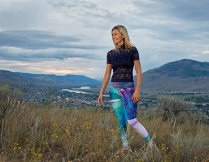 The artist, Kristina Benson poses for a portrait showcasing a pair of her wearable art leggings, Kamloops, British Columbia, Canada