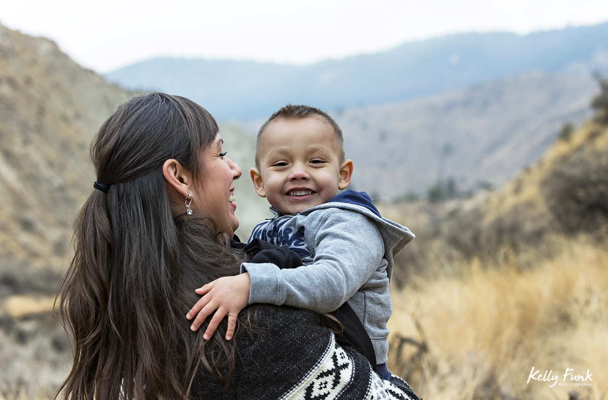 A mother holds her smiling son during a family shoot, near Kamloops, British Columbia, Canada