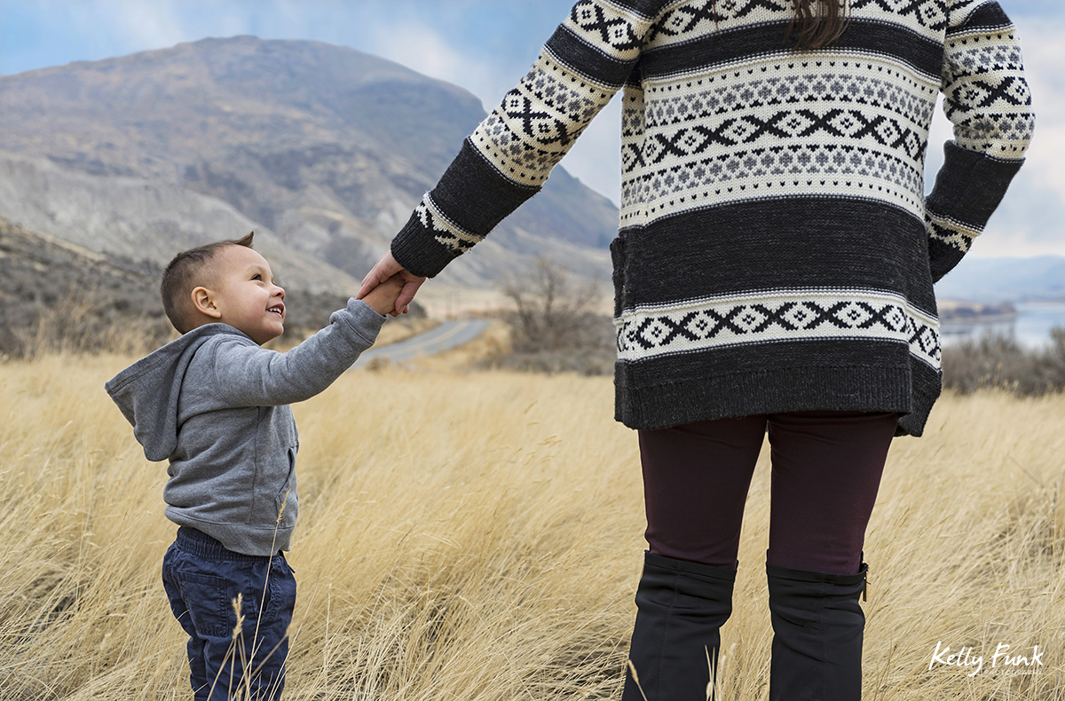 A mother leads her son through the tall grass during a family shoot, near Kamloops, British Columbia, Canada