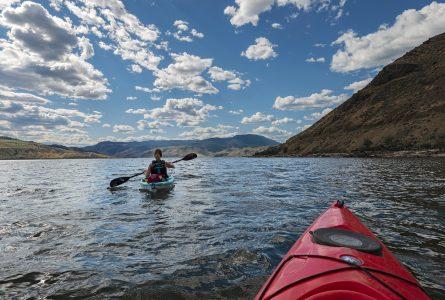 Kayakers travel west on Kamloops Lake, Thompson Okanagan region of British Columbia, Canada