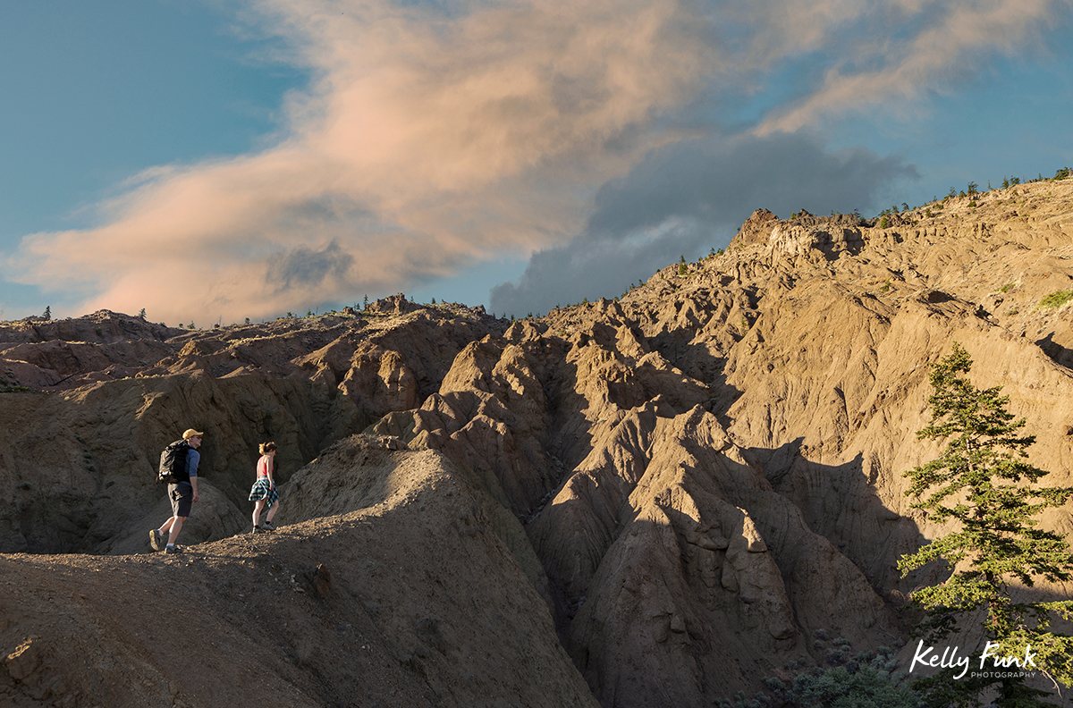 Hikers enjoying sunset in the rugged desert terrain region of British Columbia, Thompson Okanagan region, Canada