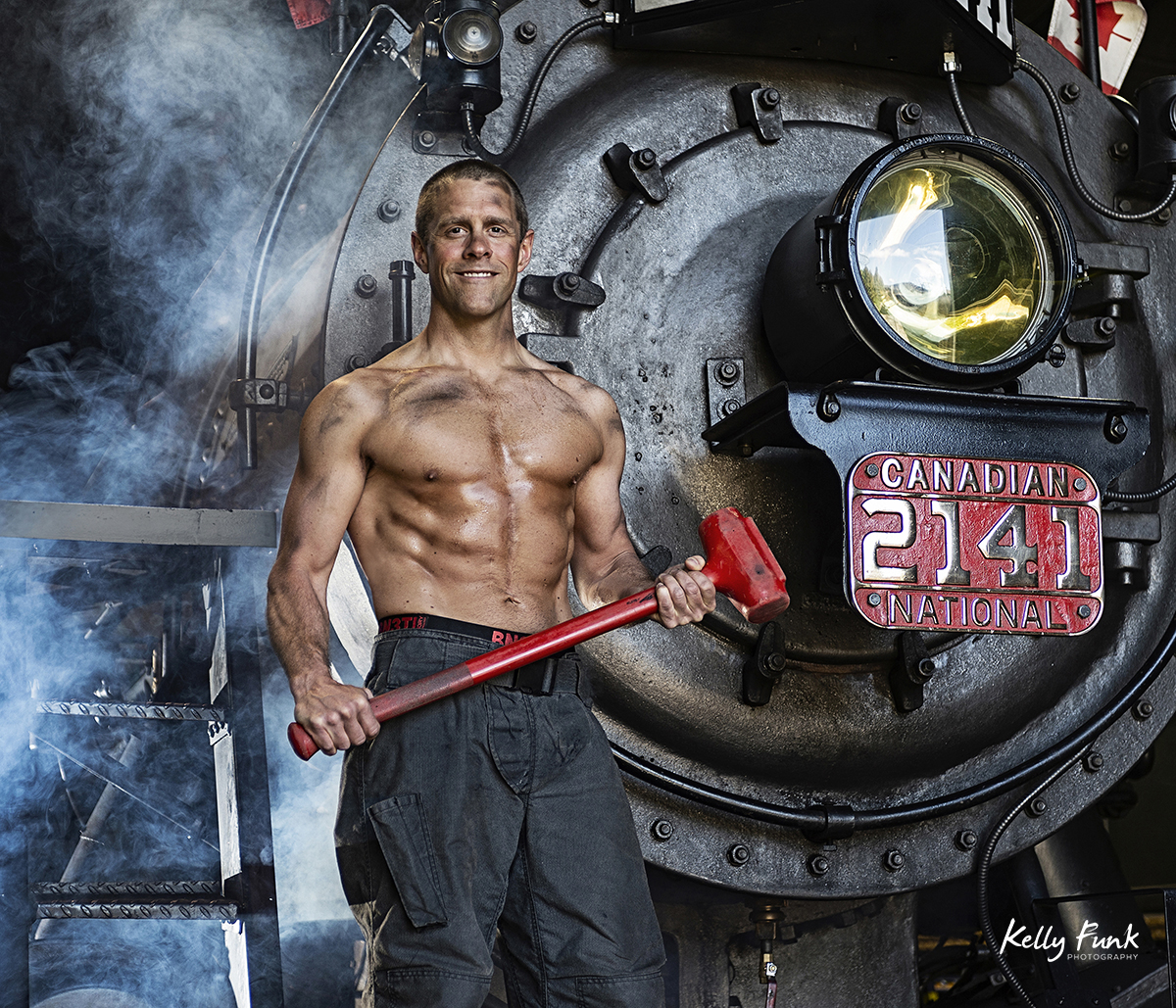 a good looking fire fighter poses for a commercial portrait during shooting for the 2019 Kamloops fire fighters calendar, Thompson Okanagan region, British Columbia, Canada