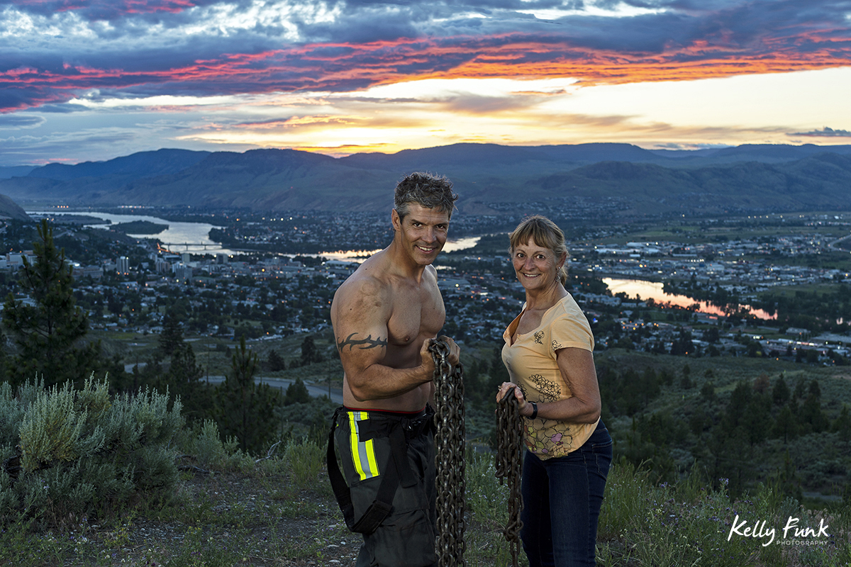 A technical photography assistant and a fire fighter pose during shooting for the 2019 Kamloops fire fighters calendar, Thompson Okanagan region, British Columbia, Canada