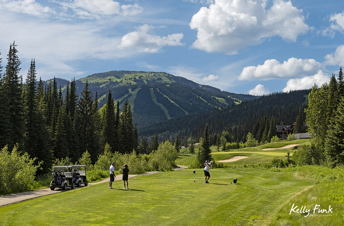 A man tees off at the 14th hole, while friends look on at the Sun Peaks Resort golf course, north east of Kamloops, British Columbia, Thompson Okanagan region, Canada