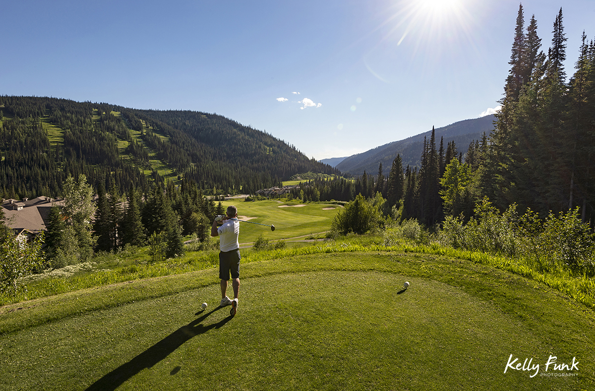 A man tees off at the elevated 16th hole at the Sun Peaks Resort golf course, north east of Kamloops, British Columbia, Thompson Okanagan region, Canada