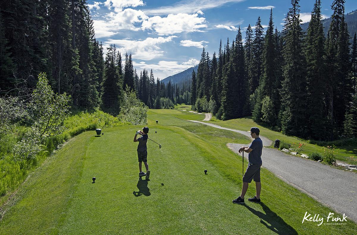 Two boys tee off at the Sun Peaks Resort golf course, north east of Kamloops, British Columbia, Thompson Okanagan region, Canada