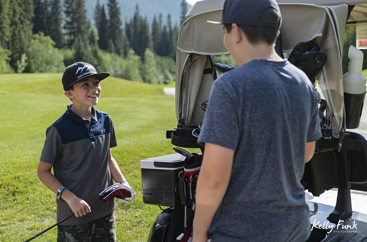 Two boys laugh while golfing at the Sun Peaks Resort golf course, north east of Kamloops, British Columbia, Thompson Okanagan region, Canada