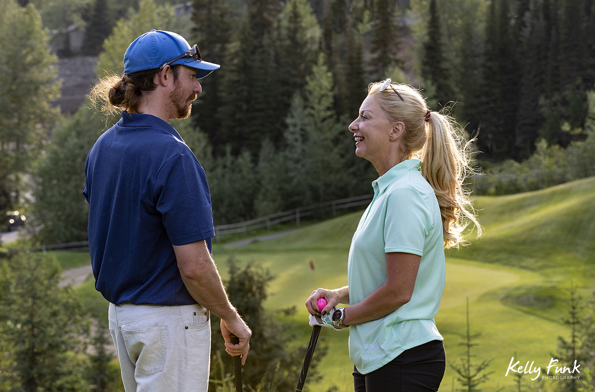 A couple talks about tee off approaches at the Sun Peaks Resort golf course, north east of Kamloops, British Columbia, Thompson Okanagan region, Canada