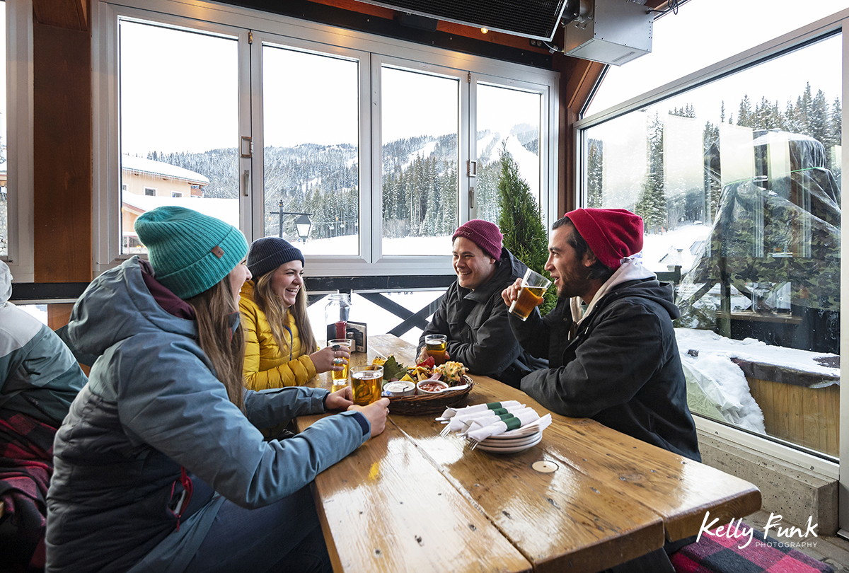 enjoying food and drinks after a ski day at the new Bottom's enclosed patio at Sun Peaks Resort during a tourism marketing shoot, British Columbia, Thompson Okanagan region, Canada