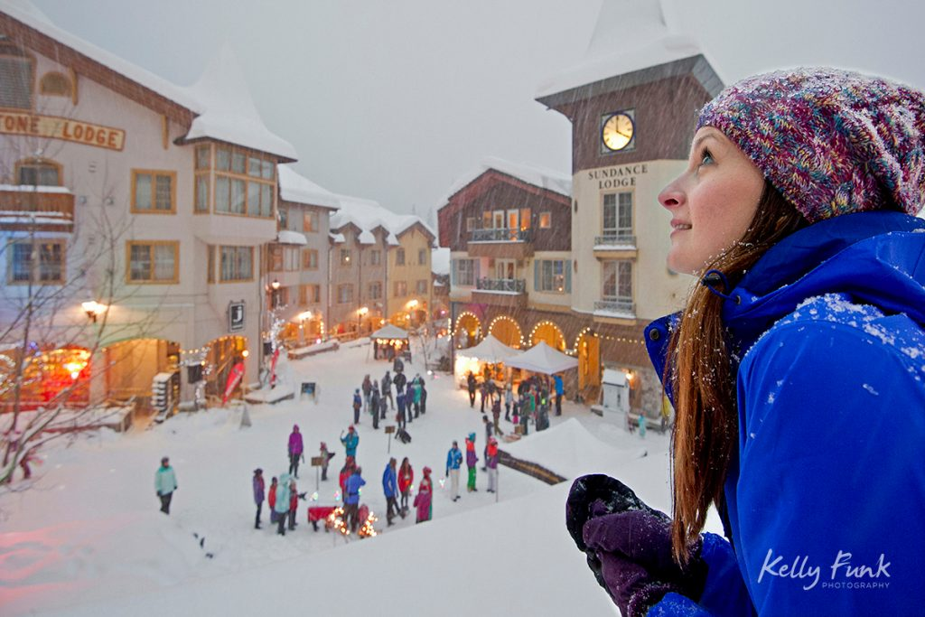 A young woman checks out the snow and festivities at Sun Peaks Resort, Sun Peaks, British Columbia, Thompson Okanagan region, Canada.