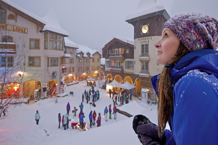 A beautiful woman takes in the view of Sun Peaks Resort's village from the balcony of the Sun Peaks Grand hotel, near Kamloops, British Columbia, Canada, Thompson Okanagan region