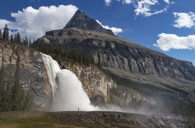 A hiker is dwarfed at Emperor falls, Mt. Robson Provincial park, British Columbia, Canada