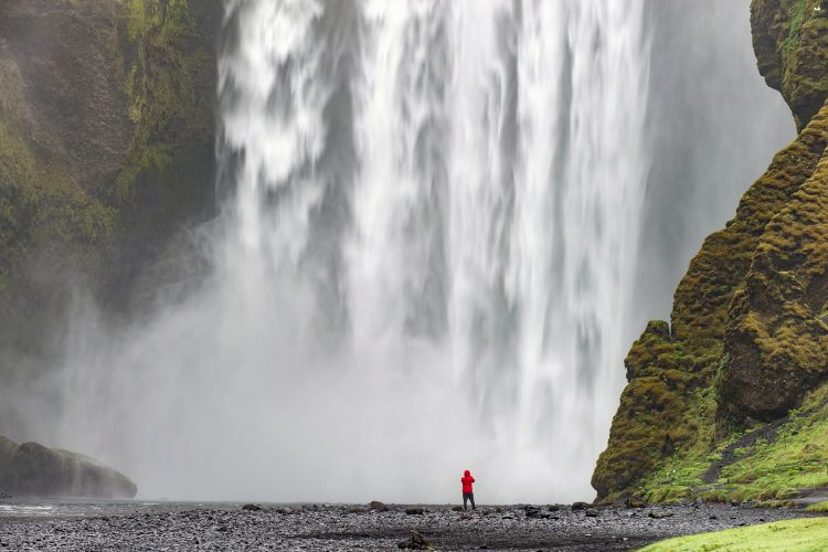 A tourist takes in the world famous Skogafoss, south Iceland, Europe