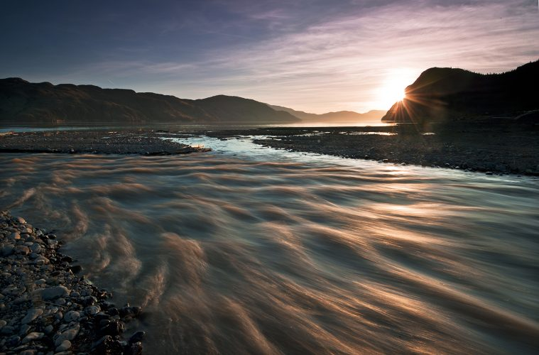 Tranquille river flows into Kamloops lake during spring run off at sunset, near Kamloops, Thompson Okanagan region, British Columbia, Canada
