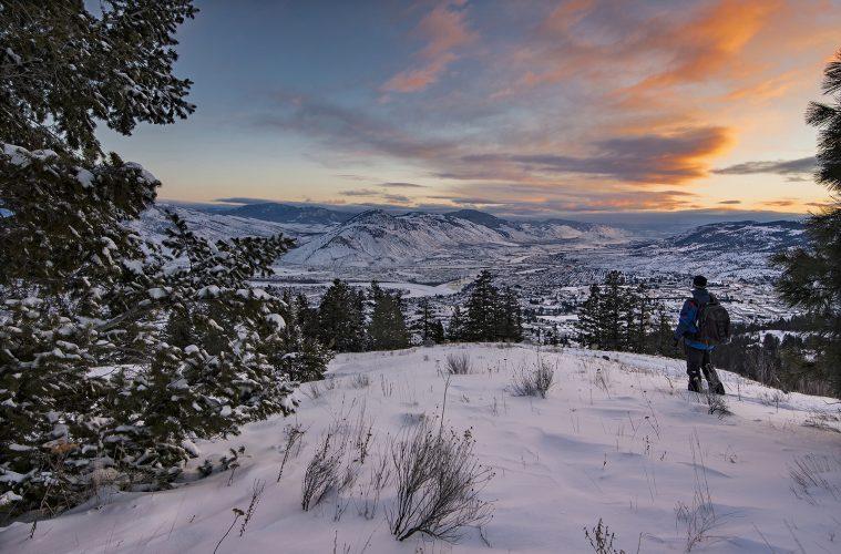 A hiker checks out the sunrise over Kamloops, BC, Thompson Okanagan region, Canada