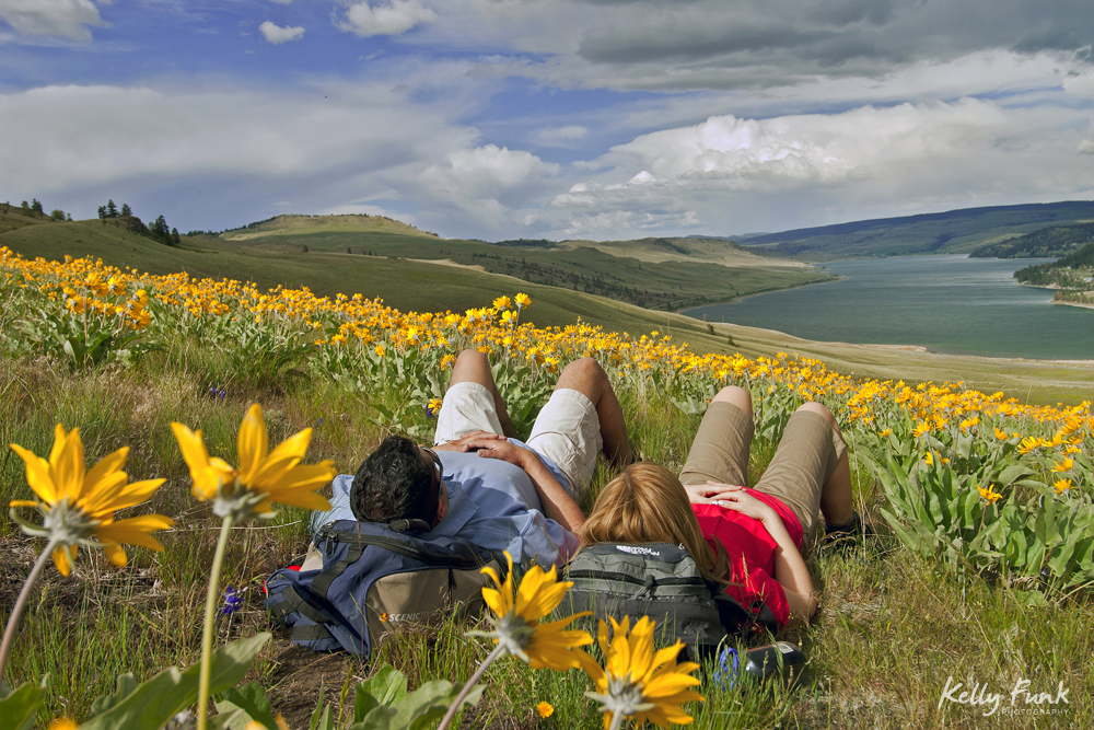 Hikers stop for a rest in the wildflowers above Stump Lake, Thompson Okanagan region, British Columbia, Canada