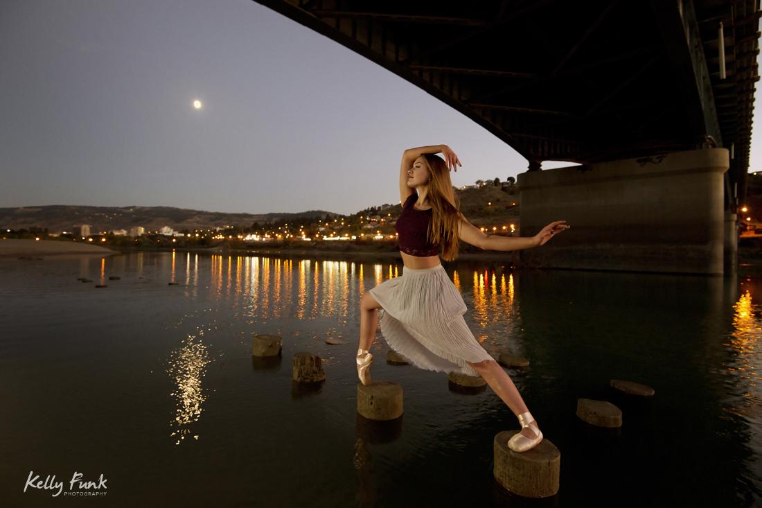 A beautiful, young ballet dancer poses under the Overlander bridge, on the Thompson river, Kamloops, Thompson Okanagan region, British Columbia, Canada